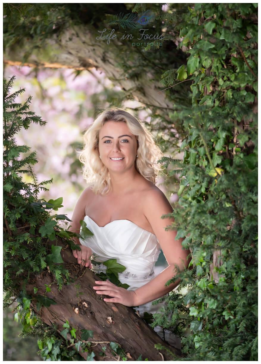 bridal photo bride looking though trees Life in Focus Portraits wedding photographer Rosslea Hall Hotel Rhu Loch Lomond