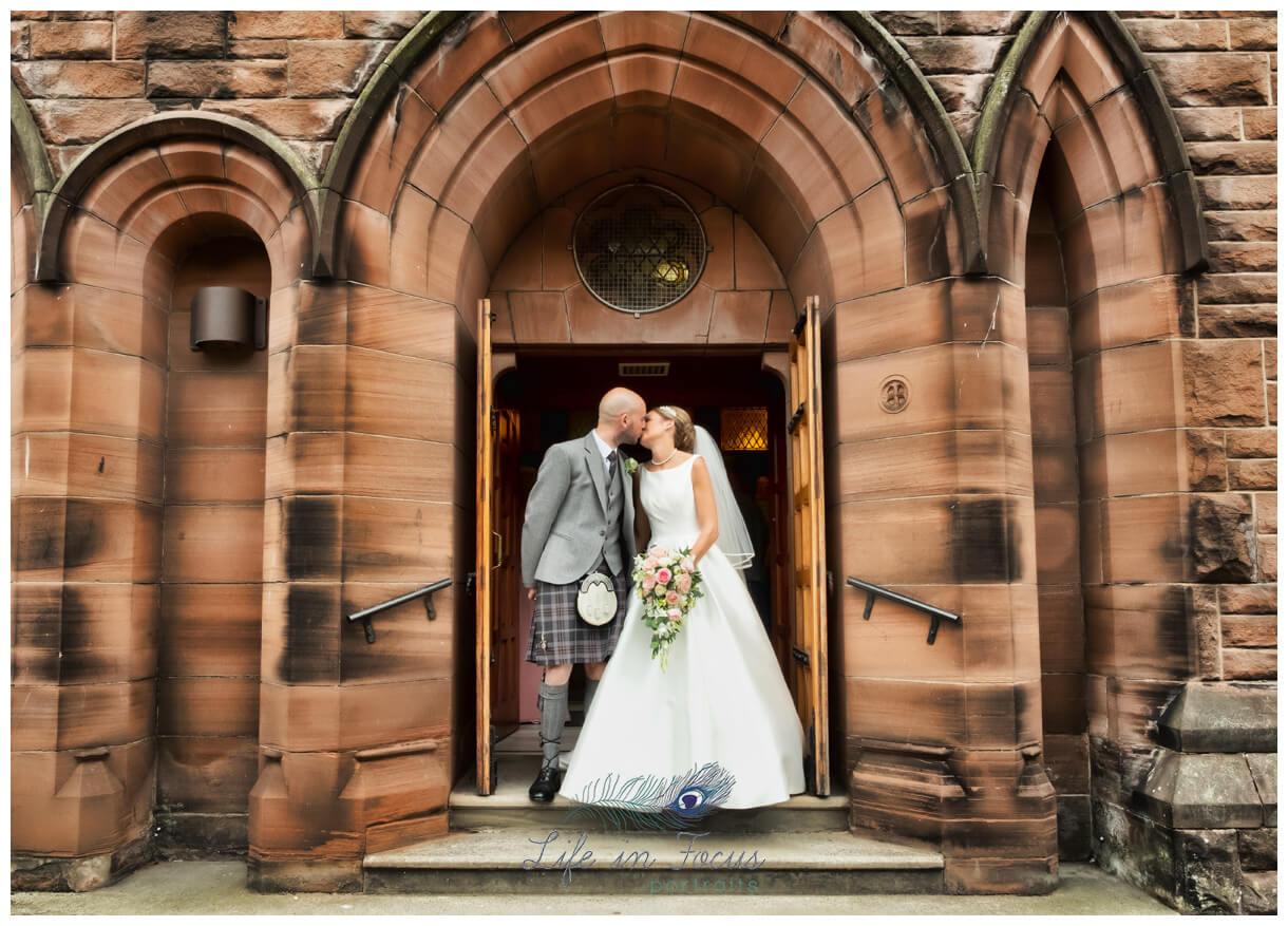 bride and groom kiss on church steps St Patrick's church Dumbarton Life in Focus Portraits wedding photography Dumbarton West Dunbartonshire
