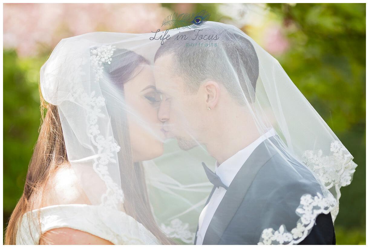bride and groom kiss under wedding veil Life in Focus Portraits wedding photographer Dunbartonshire