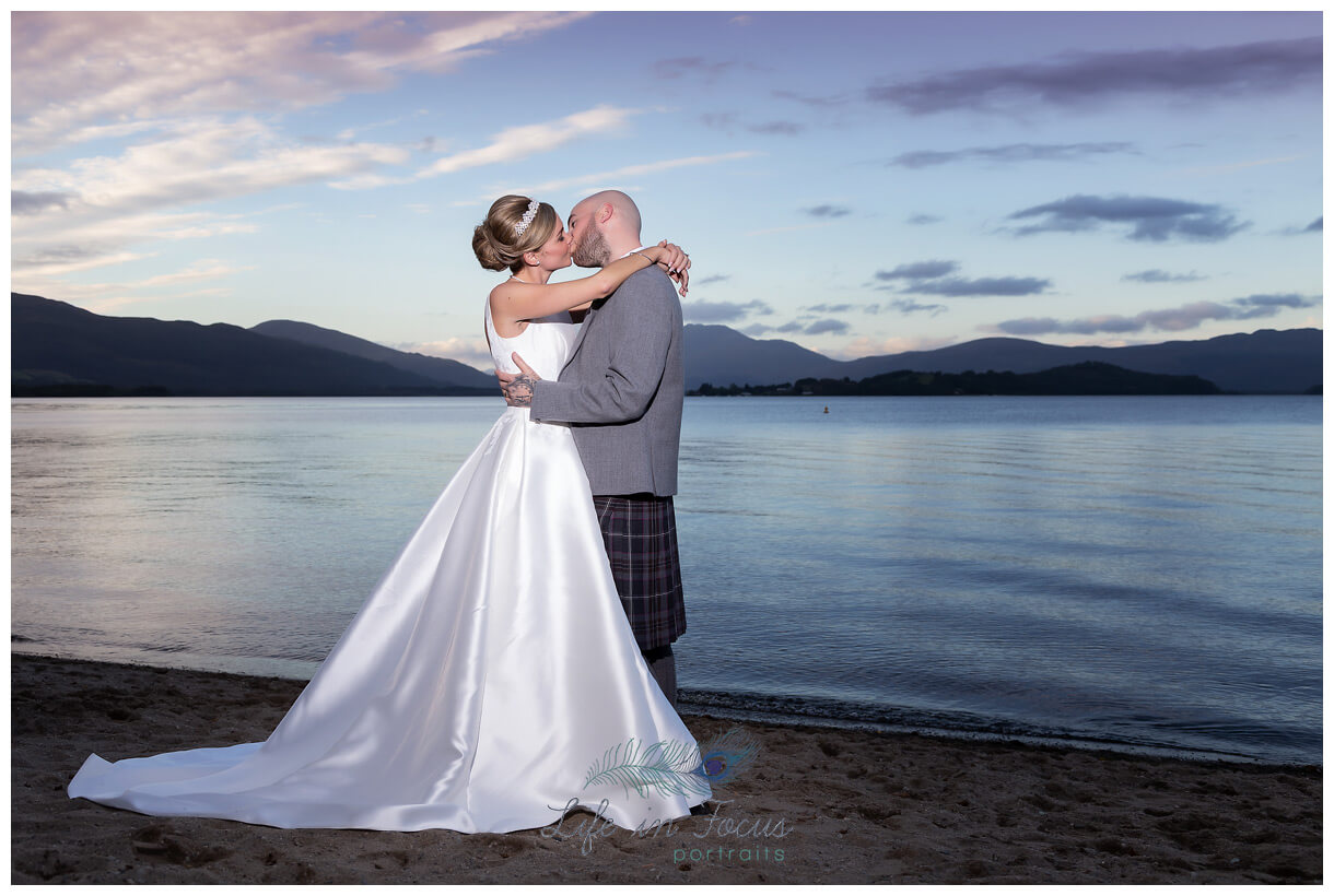 bride and groom kissing by Loch Lomond at dusk Life in Focus Portraits Wedding photographer Helensburgh Argyll and Bute