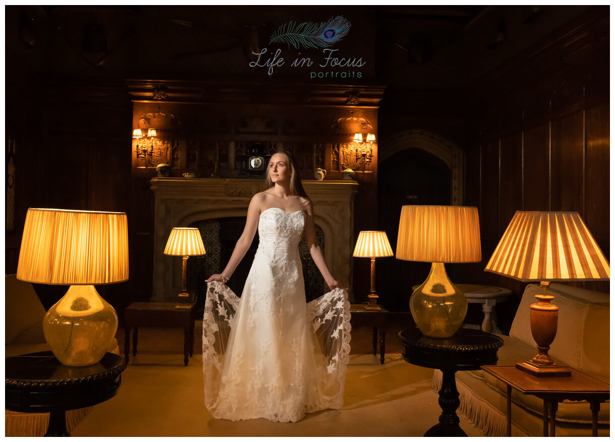 bride in castle surrounded by antique lamps Life in Focus Portraits scottish castle wedding photography Loch Lomond
