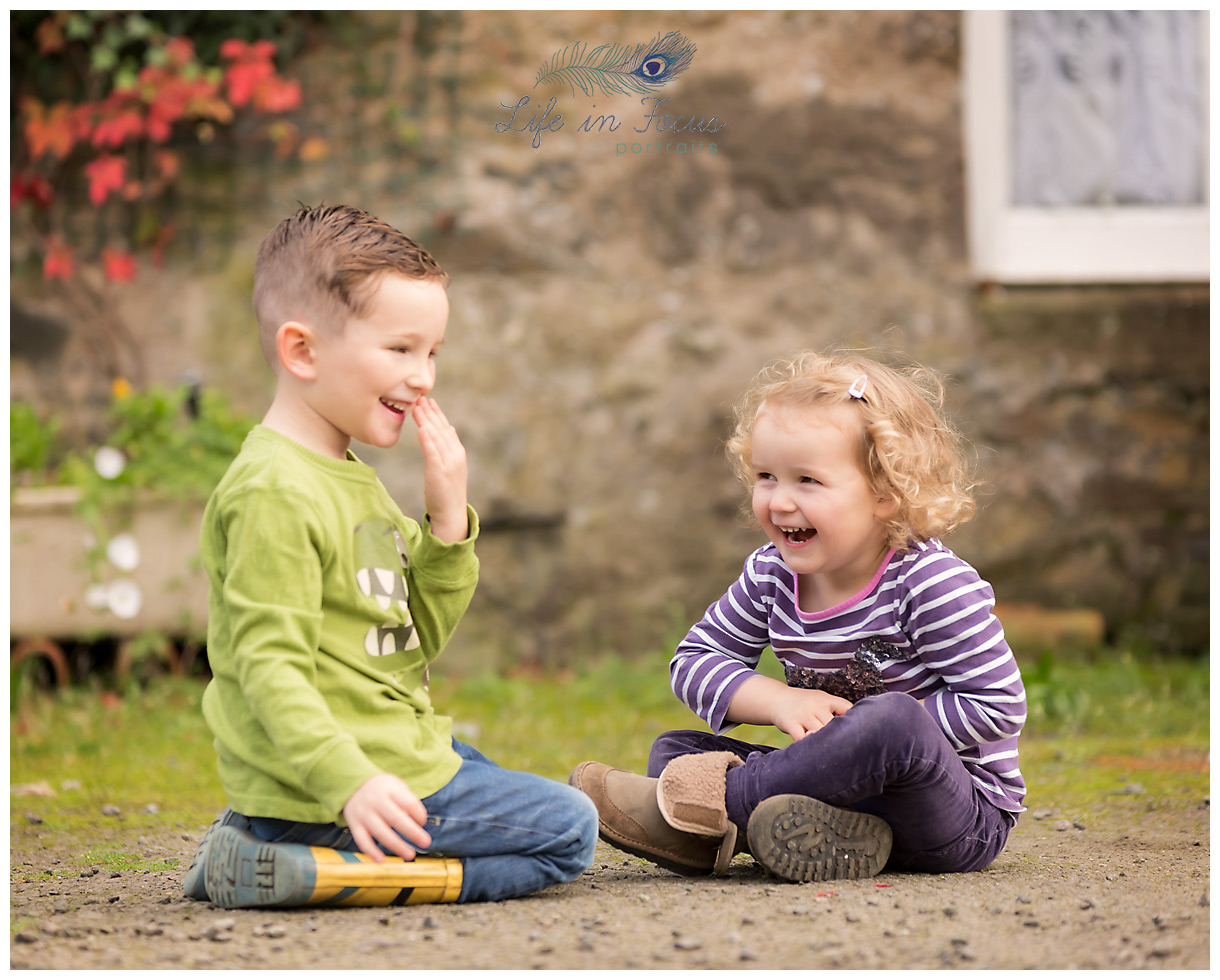 brother and sister playing and laughing farm holiday cottage luss Life in Focus Portraits family vacation photographer Loch Lomond and Trossachs national park Scotland