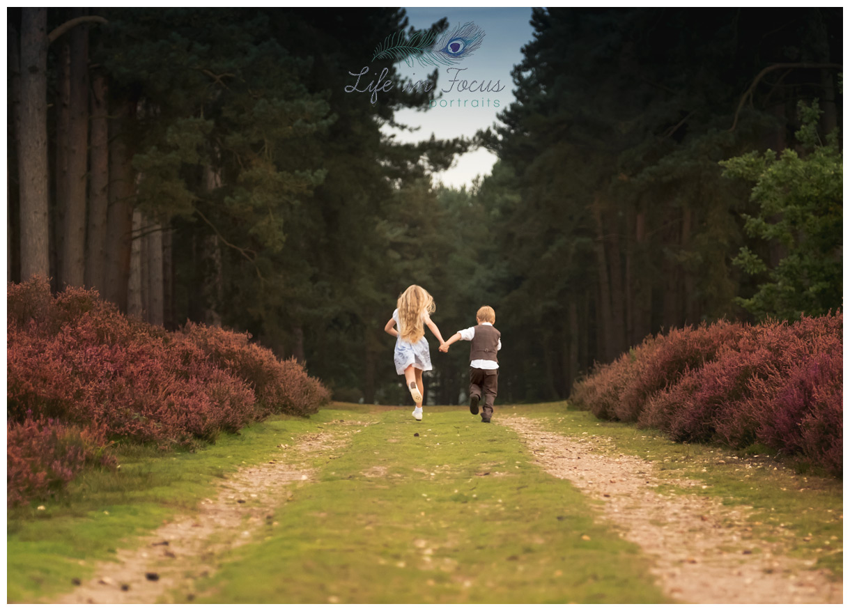 brother and sister running through forrest Life in Focus Portraits child photographer Loch Lomond and the Trossachs national park Scotland