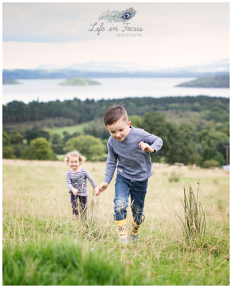 children running through field at holiday glamping site overlooking Loch Lomond Life in Focus Portraits vacation photography Luss Loch Lomond National Park Scotland