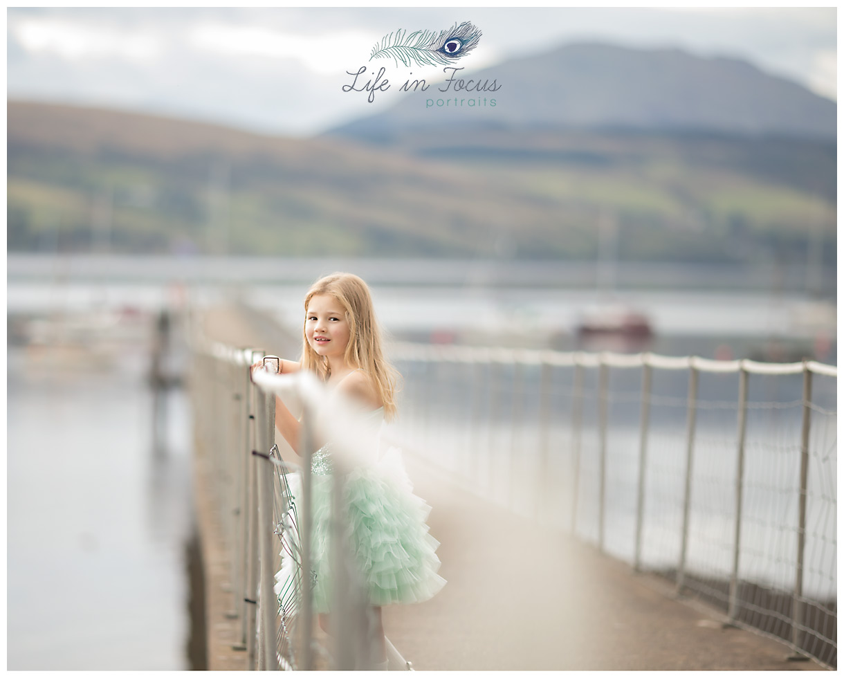 girl on pier with loch and mountains Life in Focus Portraits Helensburgh child photographer Rhu Gareloch