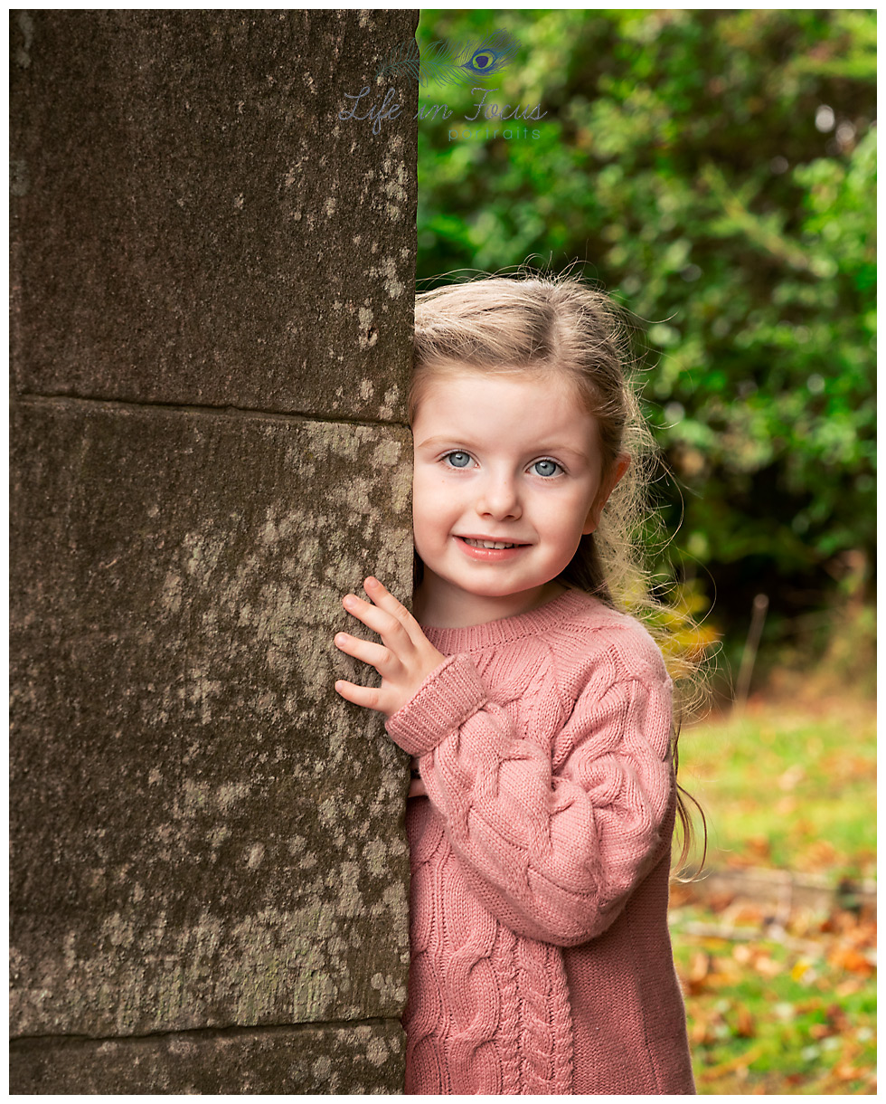 girl peeping round corner outdoor child photoshoot Life in Focus Portraits family photographer Cardross Dumbarton