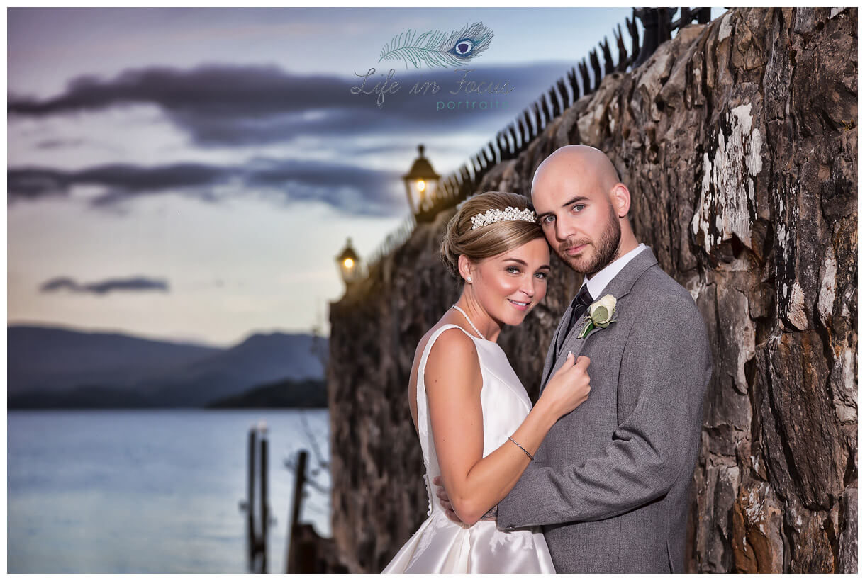newly married bride and groom by Loch Lomond at sunset Life in Focus Portraits wedding photos Helensburgh Argyll and Bute
