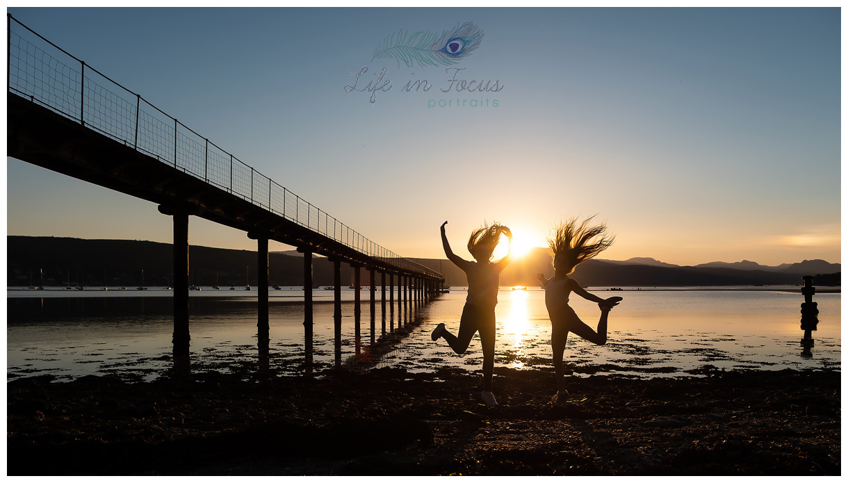 silhouette photo of friends leaping into air at sunset by lochside pier Life in Focus Portraits outdoor child photos Rhu Garelochhead Rosneath Cove