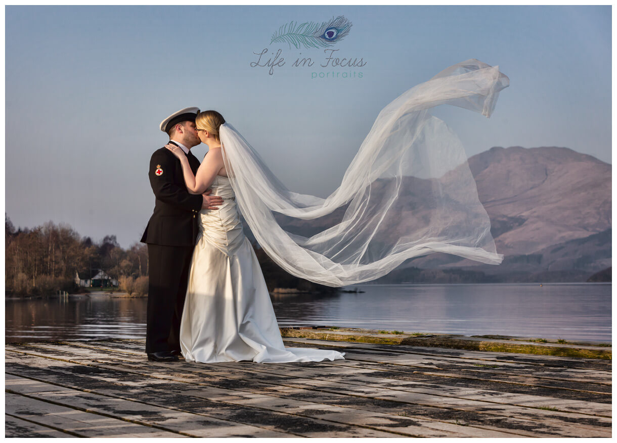 wedding photo Royal Navy married couple on Luss pier with Ben Lomond as natures backdrop Life in Focus Portraits wedding photographer Loch Lomond