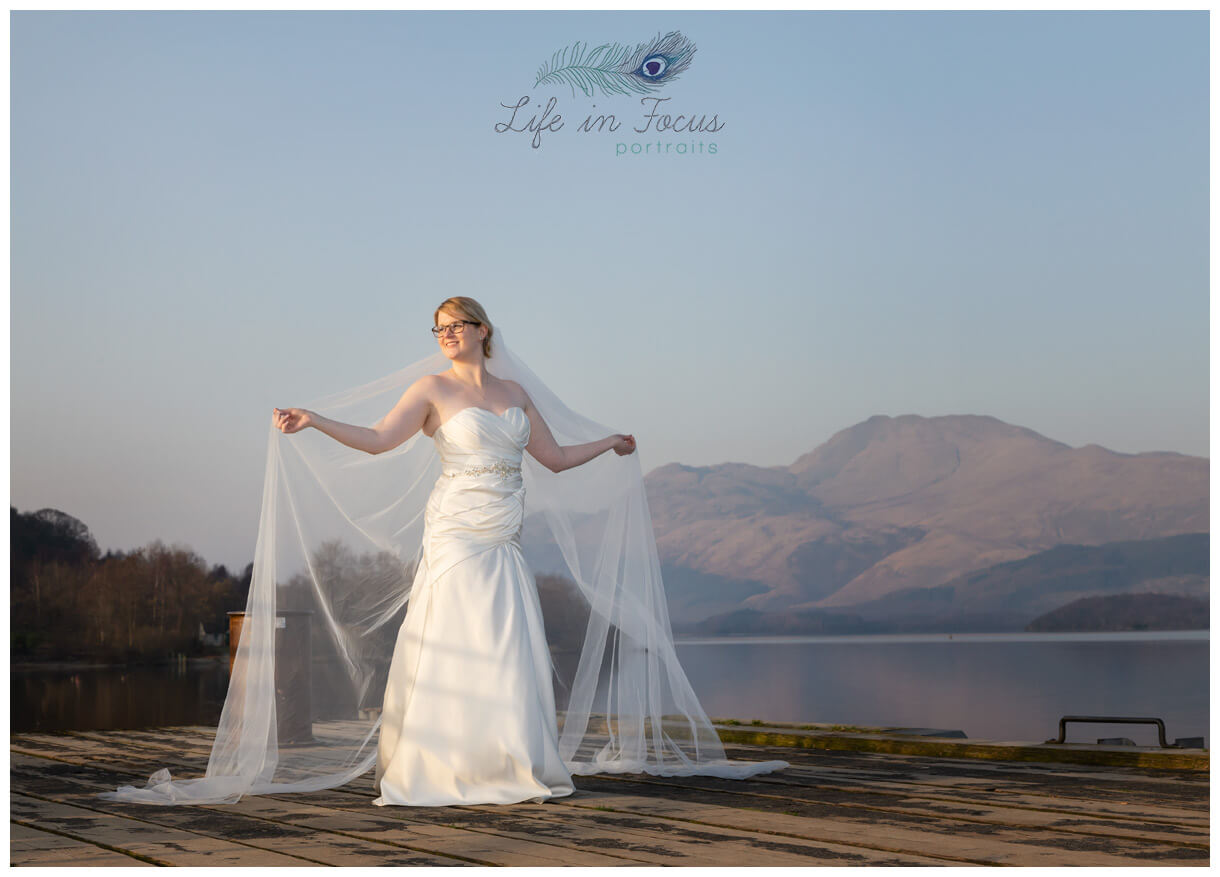 wedding photo bride holding veil on Luss pier in front of Ben Lomond Life in Focus Portraits wedding photography Lodge on Loch Lomond