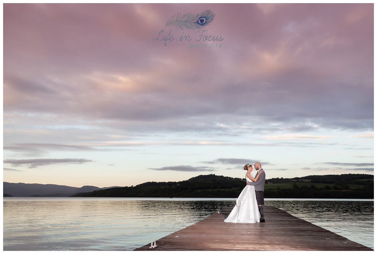 wedding photo newly married bride and groom on pier at Duck Bay Hotel at sunset Life in Focus Portraits wedding photographer Helensburgh Loch Lomond