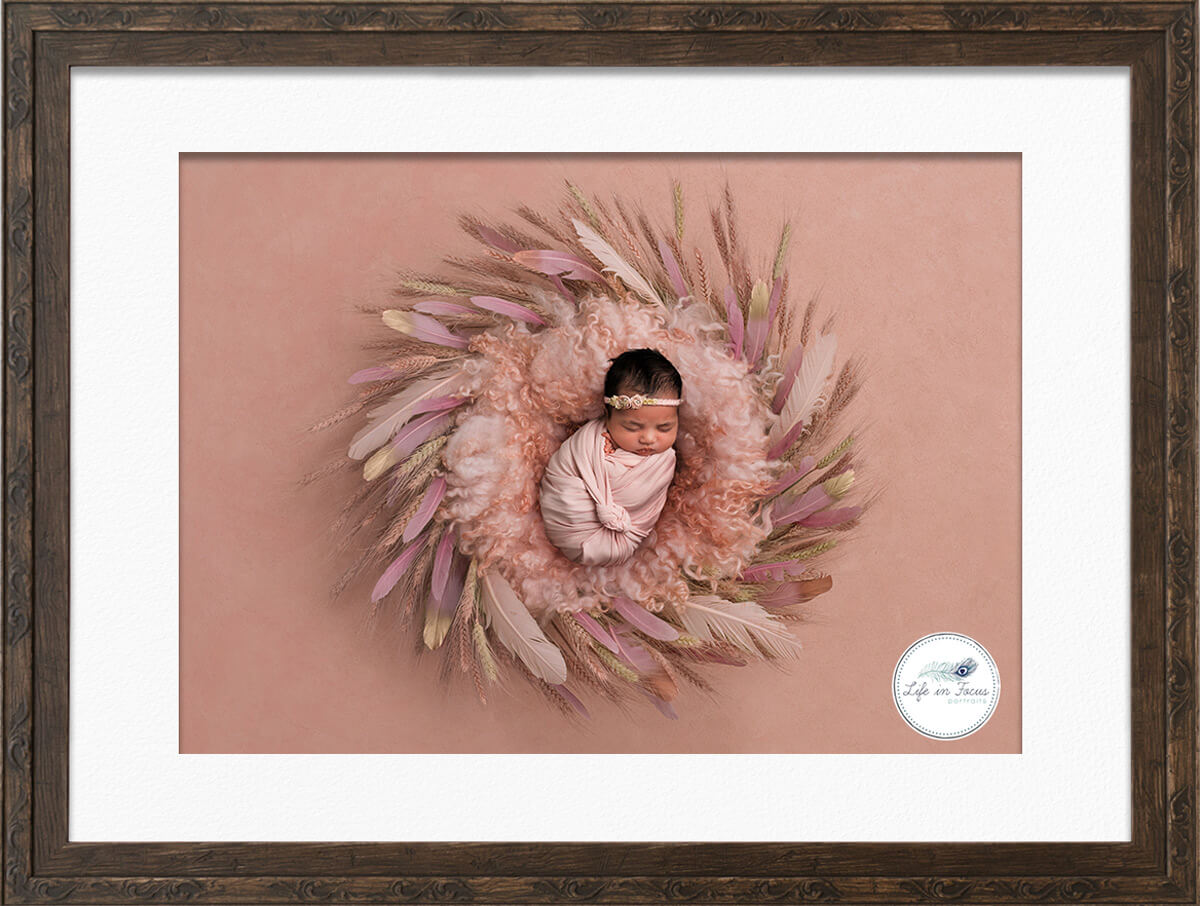 Framed photo of newborn photoshopped into feather background Life in Focus Portraits newbonr baby photography Rhu Helensburgh Roseneath
