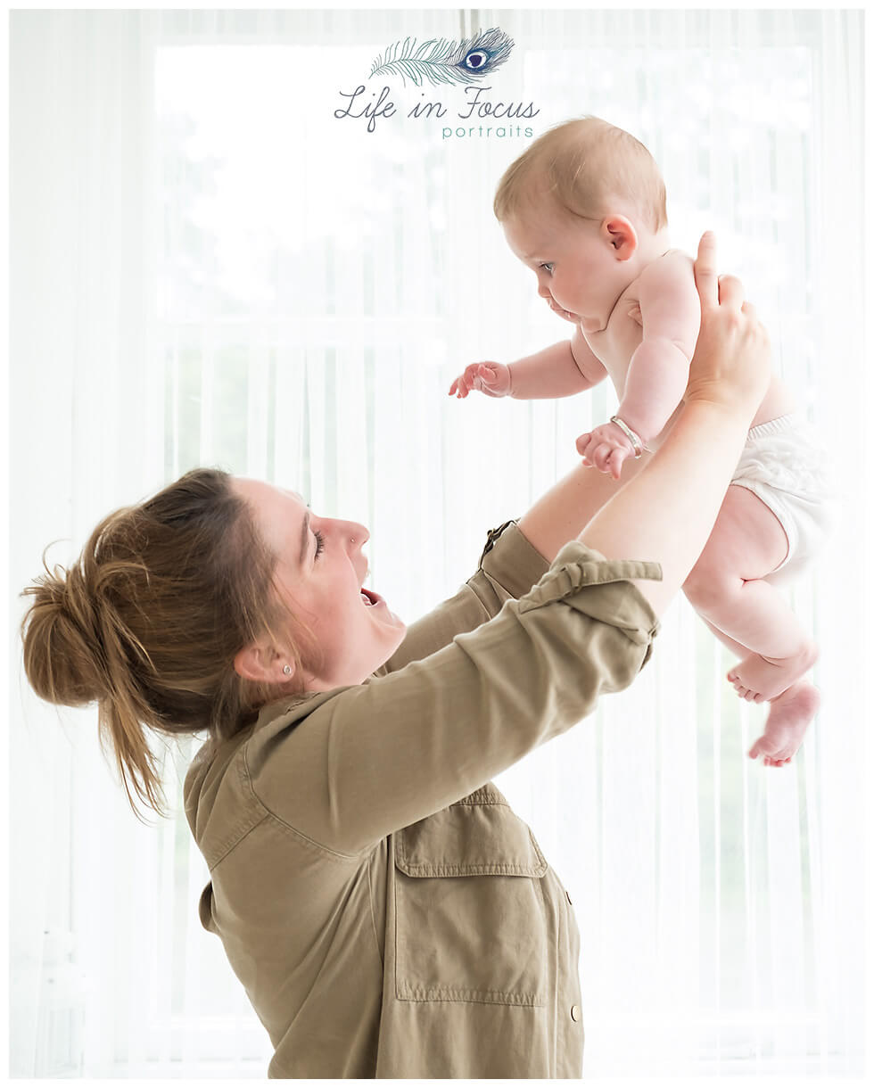 Mum ligting baby into air Life in Focus Portraits baby photography Helesburgh Luss Arrochar
