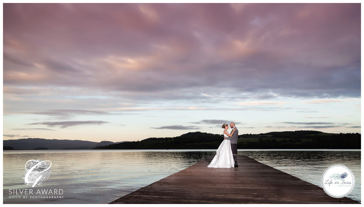 Wedding photo couple on pier Duck Bay Hotel Life in Focus Portraits award winning wedding photography Helensburgh Loch Lomond