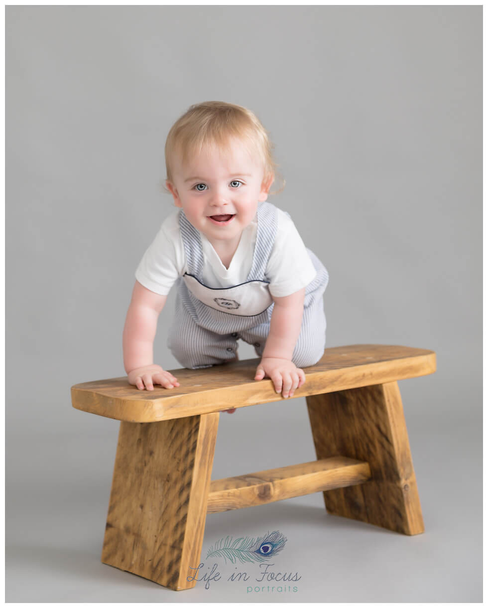 baby boy climbing on bench 1st Birthday milestone Life in Focus Portriats baby photographer Cardross