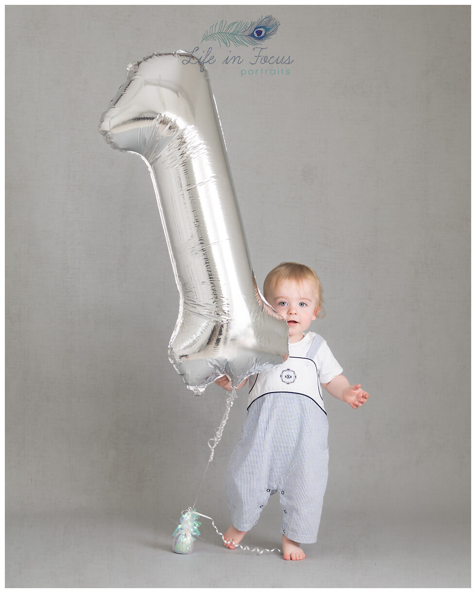 baby boy with huge number one balloon first birthday photos hoot Life in Focus Portraits Rhu baby photography studio Helensburgh
