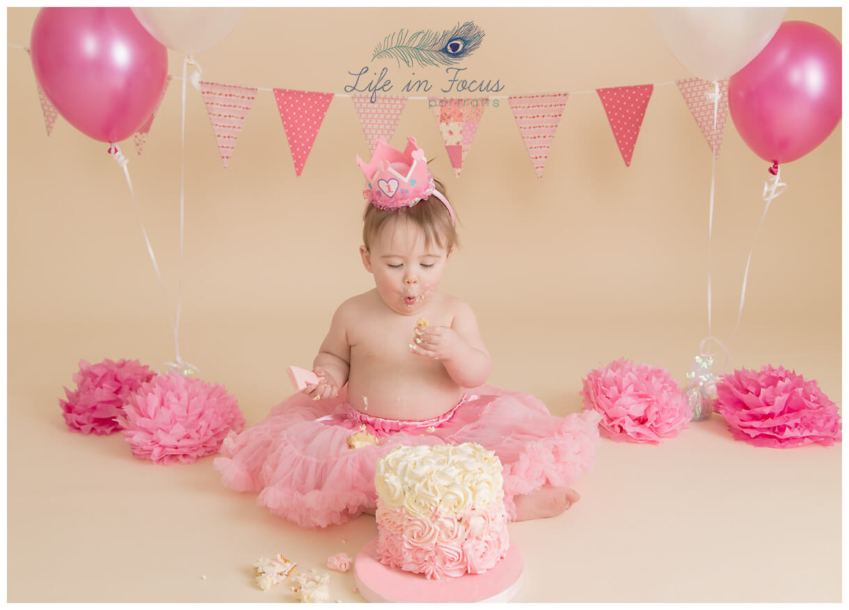 baby girl enjoying 1st birthday cake smash photo session Life in Focus Portriats studio Rhu Helensburgh
