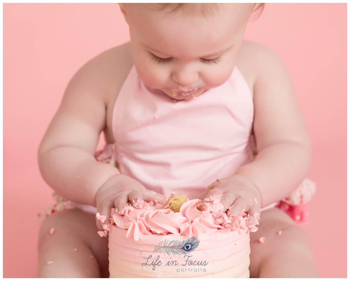 baby girl playing with first Birthday cake Life in Focus Portraits Rhu baby photographer Helensburgh Argyll and Bute