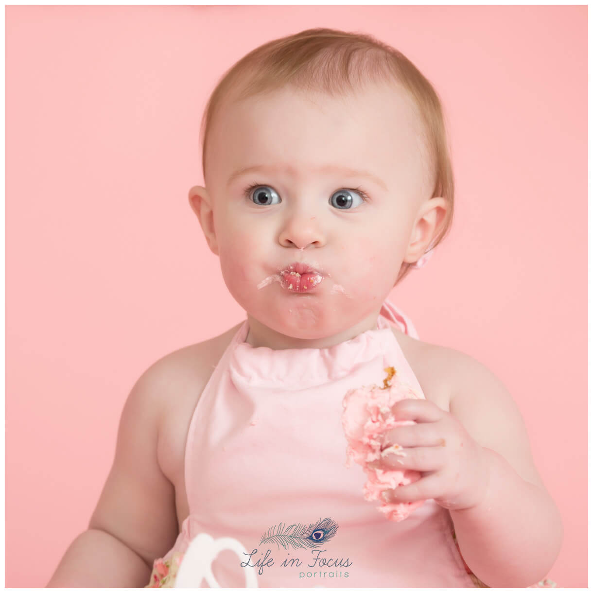 baby girl pulling cute face while eating 1st birthday cake Life in Focus Portriats baby photographer Rhu Helensburgh Cardross