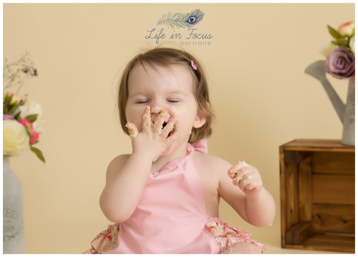 baby laughing while eating cake 1st birthday cake smash photography session Life in Focus Portraits studio childrens photographer Rhu Helensburgh