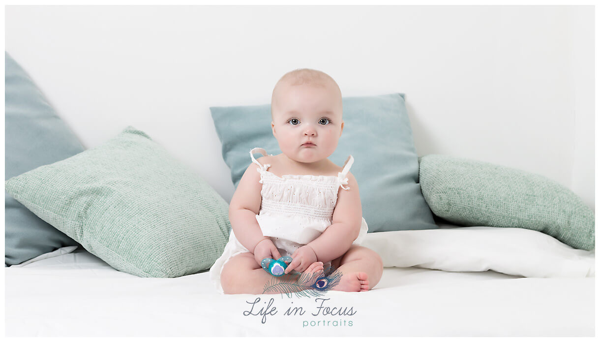baby sitting on bed holding dummy Life in Focus Portraits little sitter baby milestone photoshoot Rhu Garelochhead Rosneath
