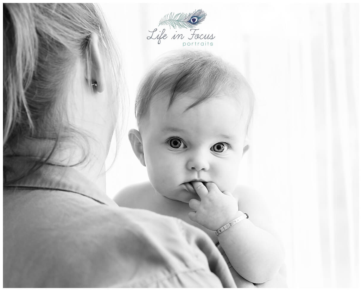 black and white photo of baby looking over Mum's shoulder Life in Focus Portraits baby photography Helensburgh Cardross