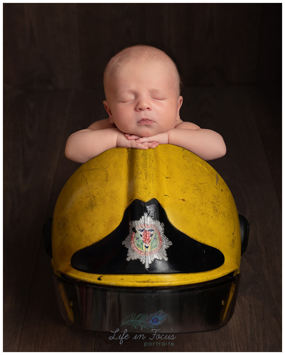 newborn baby boy on dads firefighter helmet Life in Focus Portraits newborn baby photographer Rhu Helensburgh Garelochead