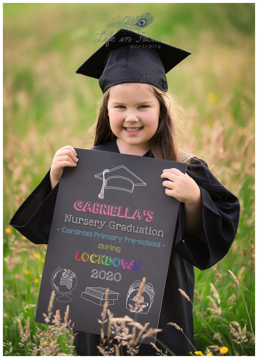 photo of little girl in nursery graduation cap and gown holding chalboard Life in Focus Portraits preschool graduation photos Helensburgh