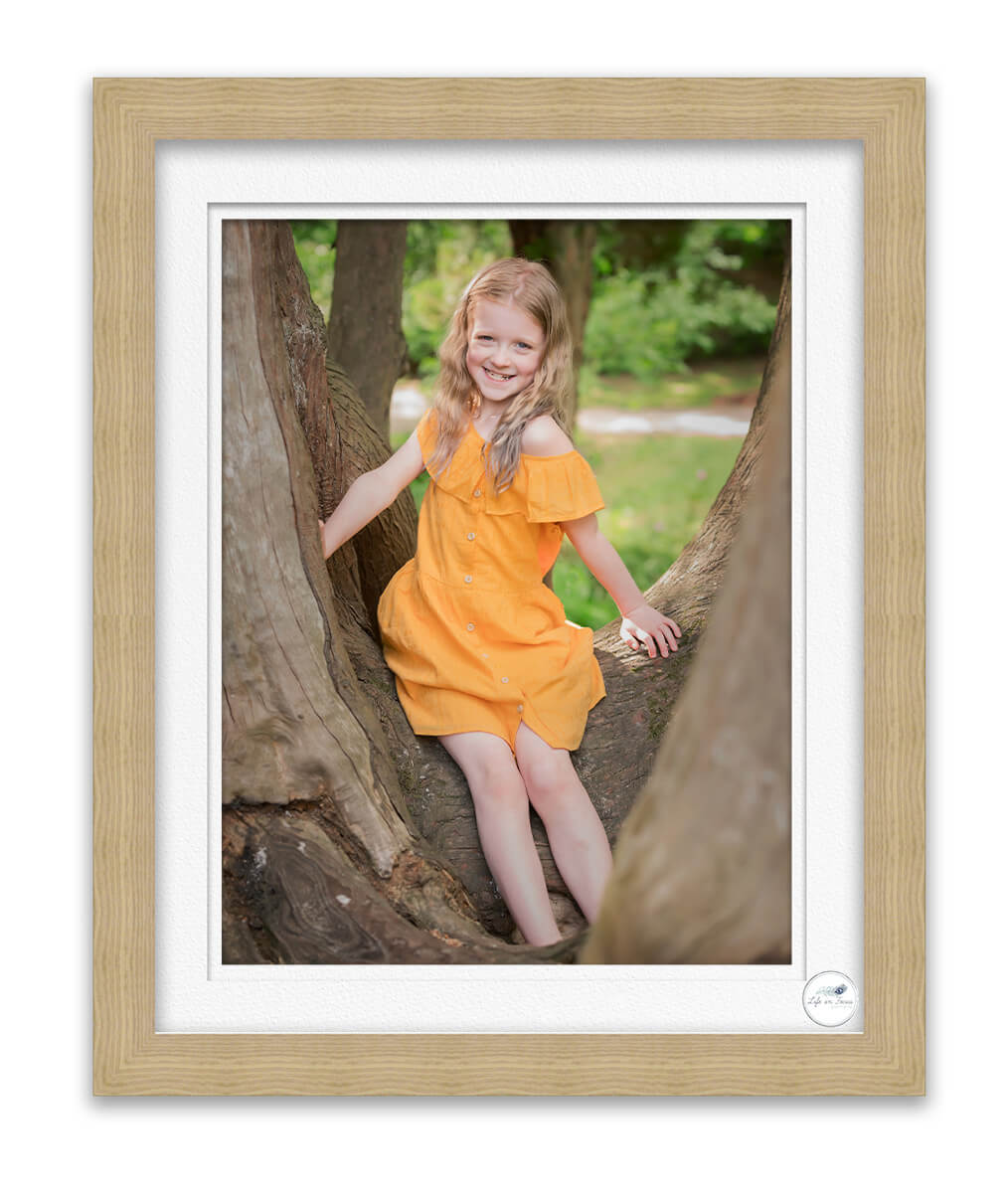 photo of young girl in tree smiling at photographer Life in Focus Portraits family outdoor photo sessions Rhu Helensburgh