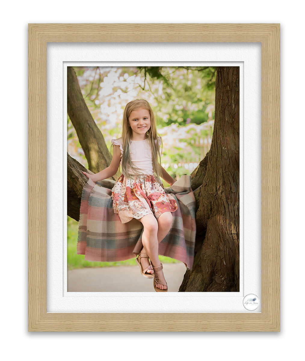 photo of young girl sitting in tree in park smiling at photographer Life in Focus Portraits family photographer Rhu Helensburgh Loch Lomond