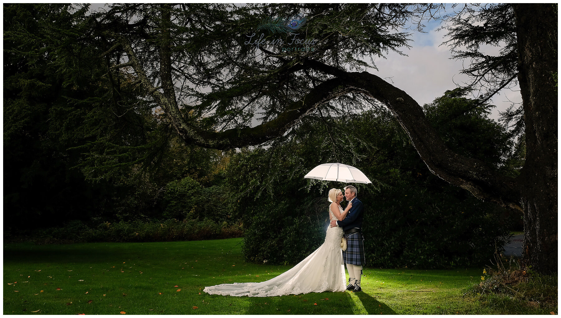 Bride and Groom embrace under umbrella Helensburgh Elopement Wedding