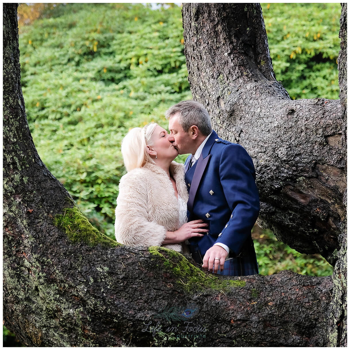 Wedding photo of bride and groom kissing under tree