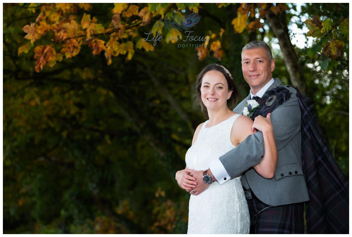 bride and groom wedding photo under autumn trees by Loch Lomond Luss