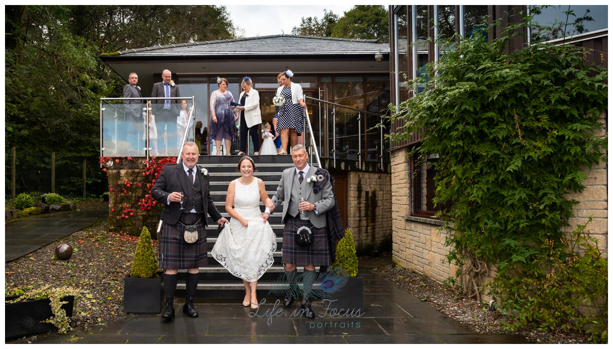 photo of bride holding up dress to walk down stairs at Lodge on Loch Lomond wedding venue