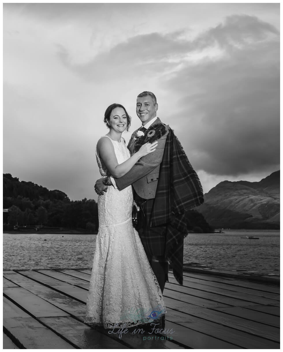 black and white photo of bride and groom on Luss pier with Ben Lomond