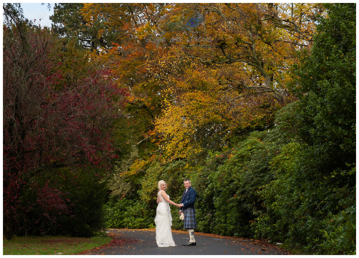 weddingphotograph os bride and groom hand in hand under autumn trees Rhu Helensburgh Argyll and Bute