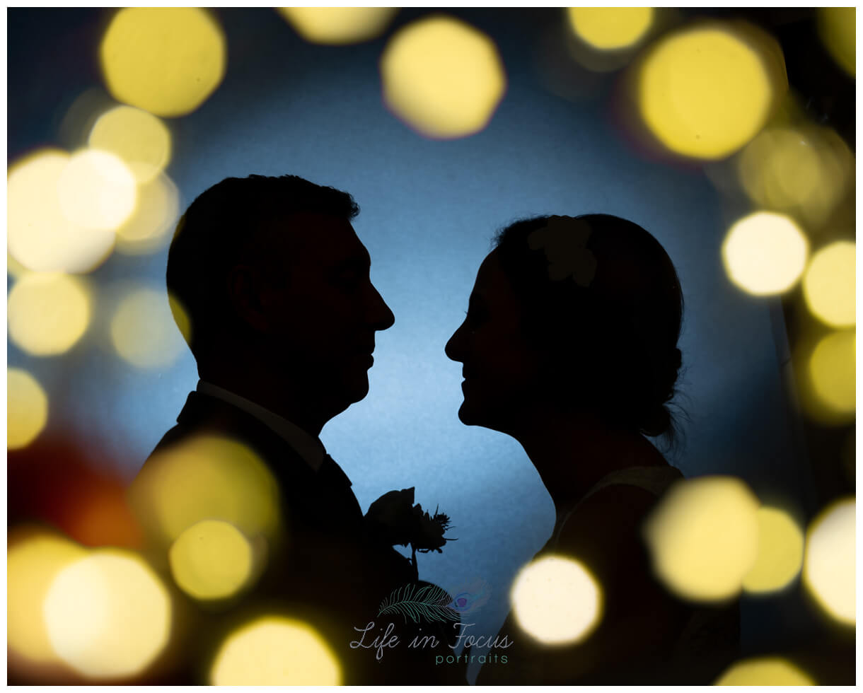 silhouette photo of bride and groom surrounded by fairy lights Loch Lomond wedding