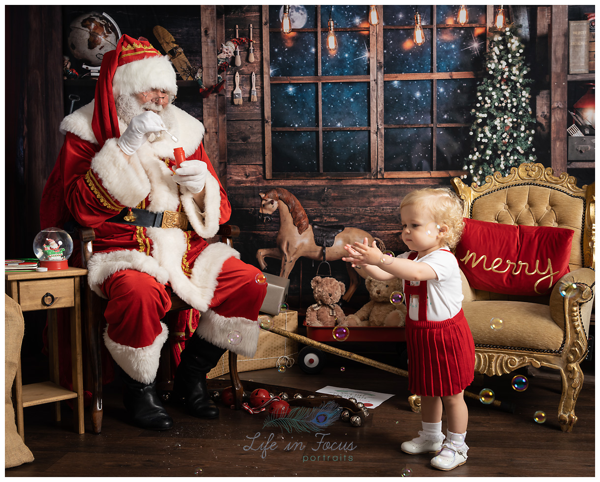 Photo of Santa blowing bubbles to little girl in red dress Christmas photoshoot at Life in Focus Portraits child photographer Helensburgh