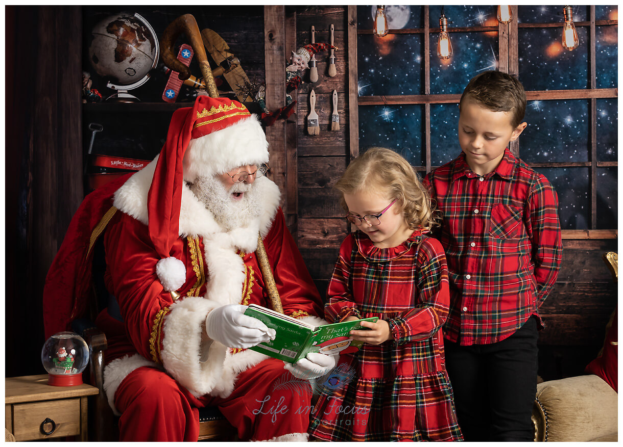 photo of boy and girl dressed in red tartan reading a book with Santa Life in Focus Portraits Christmas photoshoots Alexandria